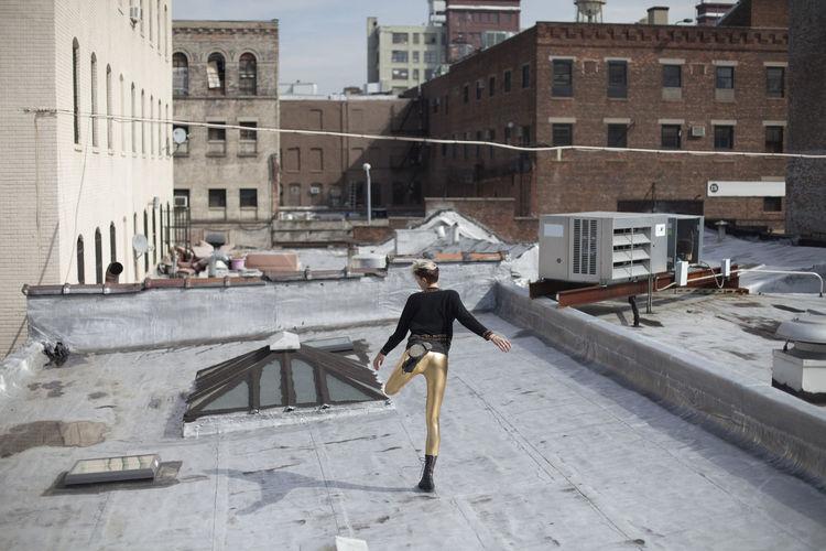 Full length of woman walking by buildings in city