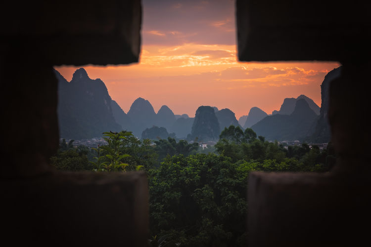 Scenic view of mountains against orange sky