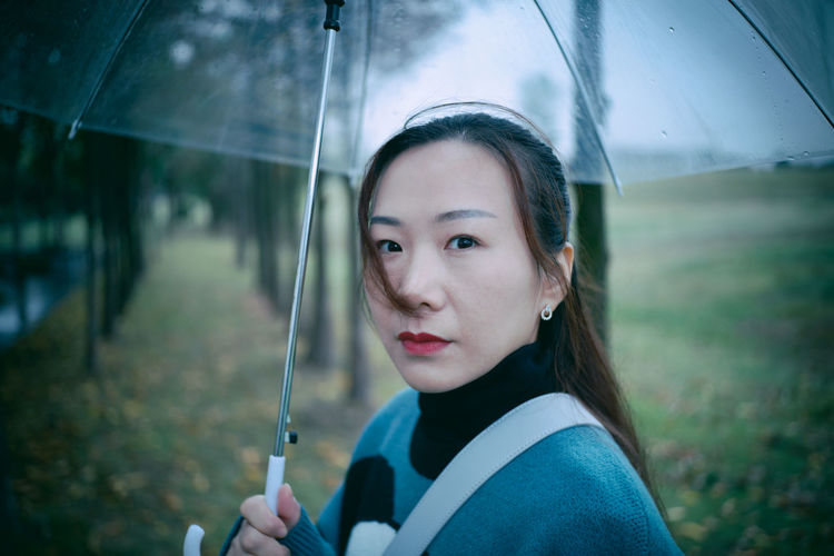 Portrait of mid adult woman holding umbrella in park