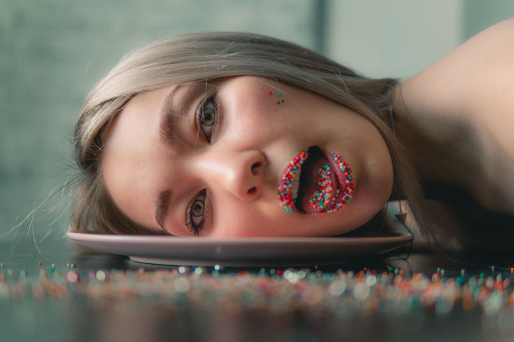 Close-up portrait of young woman with sprinkles on lips lying on plate