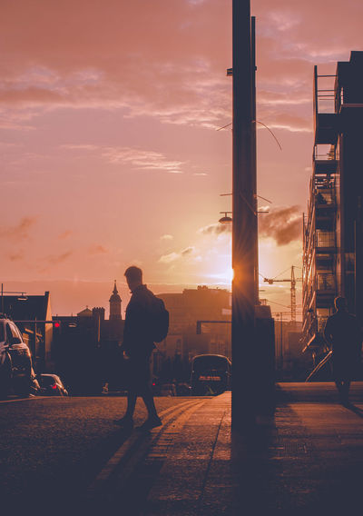 Silhouette Man Walking On Street By Buildings In City Sky During Sunset