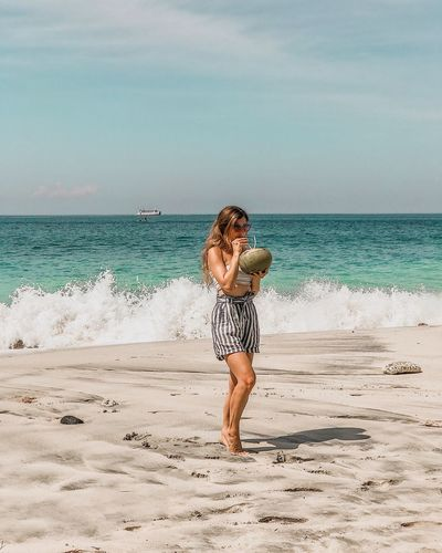 Full length of woman drinking coconut water while standing at beach against sky
