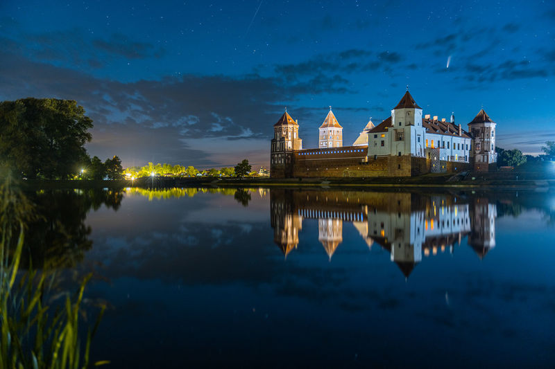 Comet neowise in a night landscape. mir castle in belarus. beautiful landscape with stars and comet