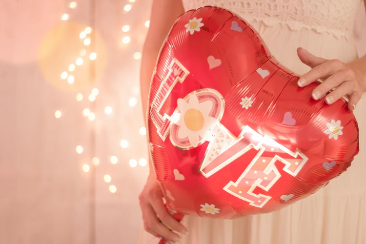 Midsection Of Bride Holding Heart Shape Balloon With Love Text Against Illuminated Lights