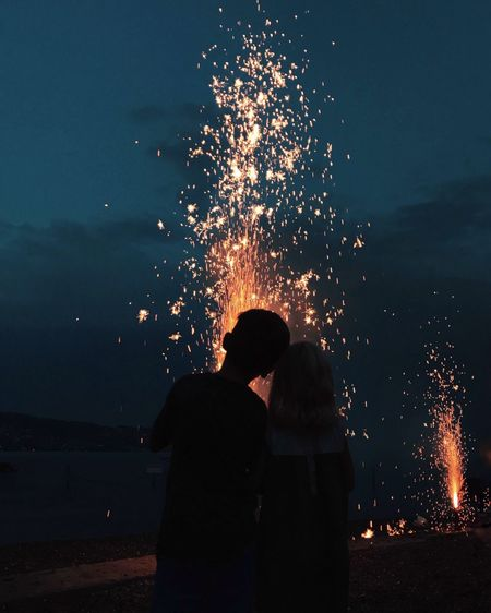 Night Rear View Burning Two People Real People Togetherness Flame Glowing Men Leisure Activity Silhouette Women Standing Heat - Temperature Sky Firework Display Outdoors Lifestyles Firework - Man Made Object Long Exposure