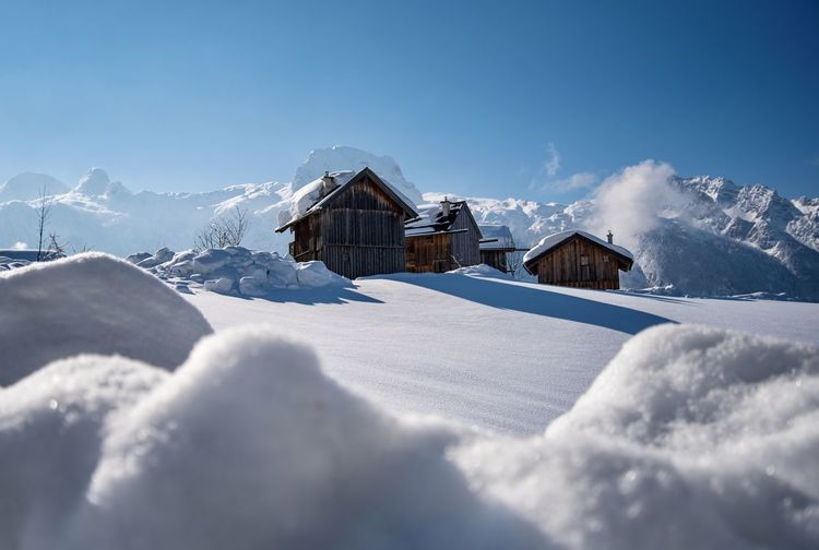 Scenic view of snow covered houses against sky