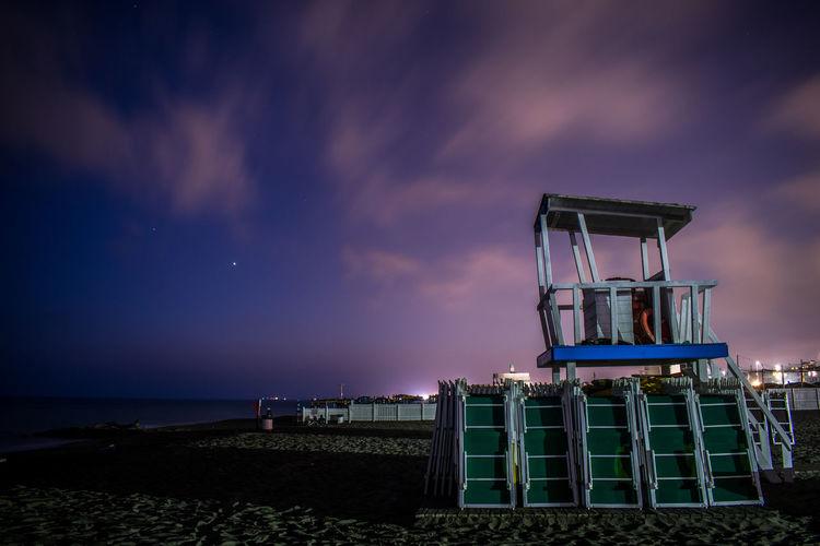 Lifeguard hut on beach against sky at night