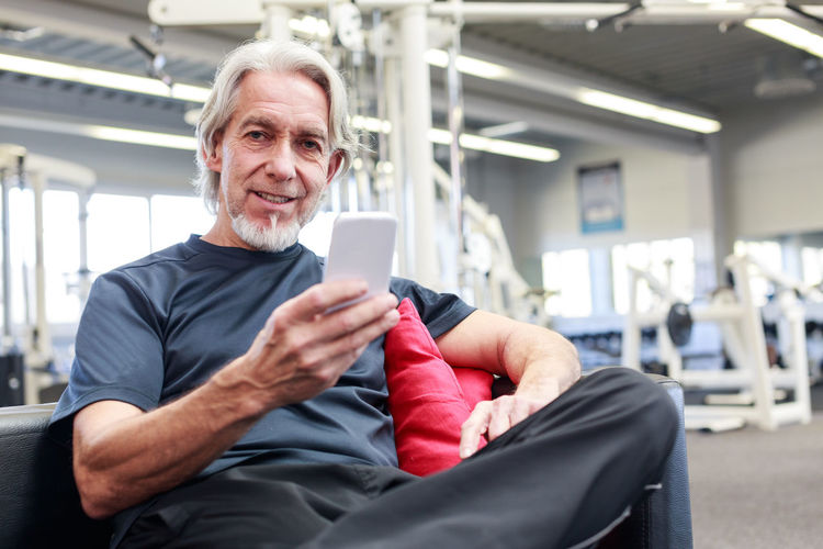 App Athlete Exercising Sportsman Activity Exercise Equipment Exercising In Nature Fitness Gym Healthy Healthy Lifestyle Indoors  Mobile Phone Retirement Plan Senior Senior Adult Senior Men Sitting Smart Phone Sport Sports Technology Workout