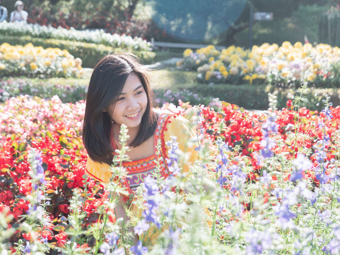 Smiling young woman looking at flowers in park