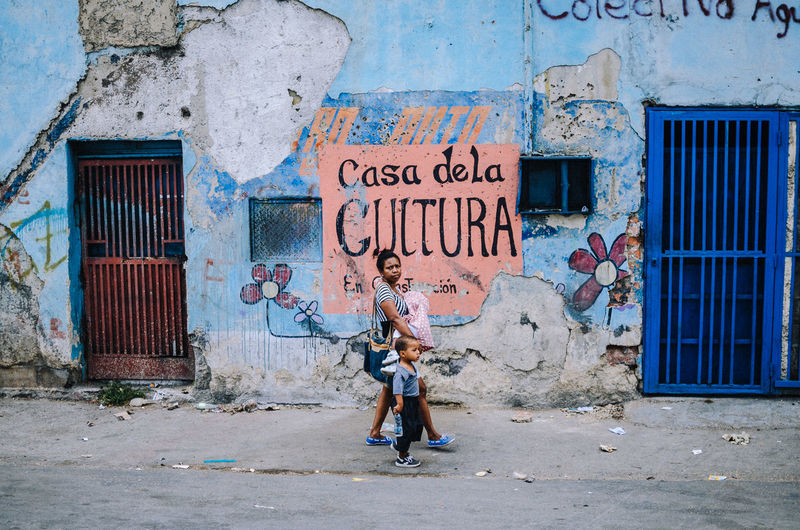 Catia, Caracas. Full Length Architecture One Person Building Exterior Day Built Structure Text Entrance Door Wall - Building Feature Building Real People Casual Clothing Western Script City Women Weathered Lifestyles Child Outdoors Deterioration Street Photography EyeEm Best Shots EyeEm Selects The Art Of Street Photography The Street Photographer - 2019 EyeEm Awards