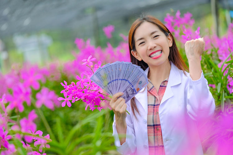 Portrait of a smiling young woman holding pink flower