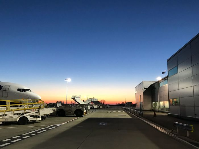 Airport runway against sky at sunset