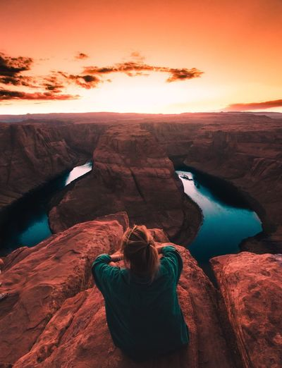 Rear View Of Woman Sitting At Horseshoe Bend Against Orange Sky