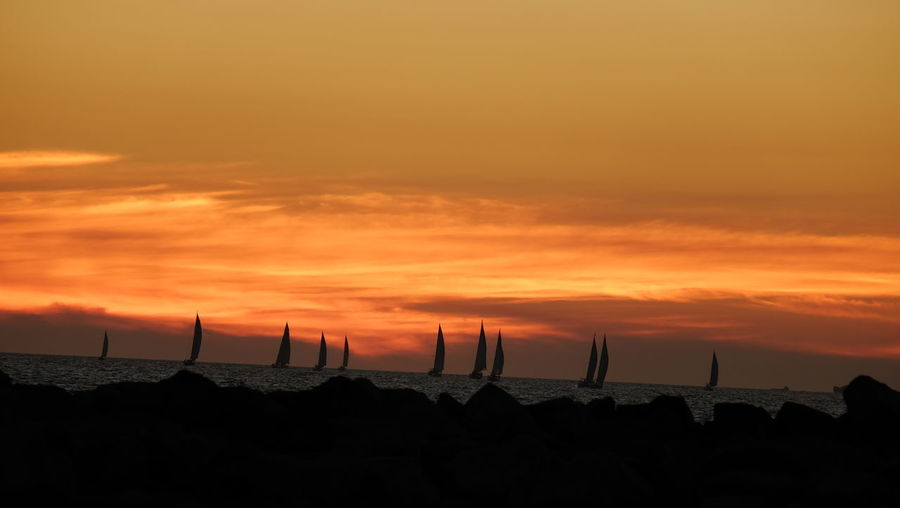 Scenic View Of Silhouette Sailboats In Sea Against Orange Sky During Sunset
