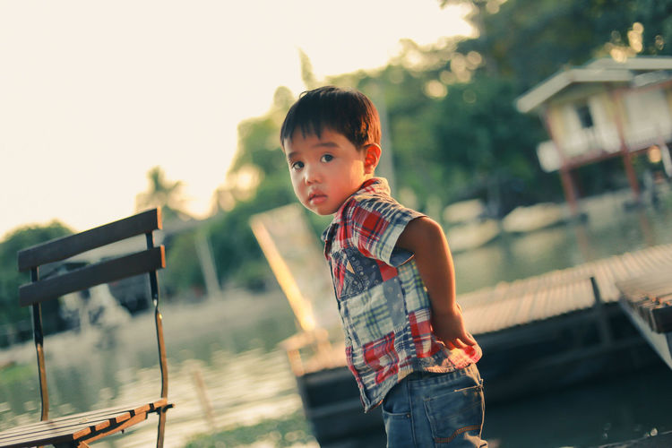 Portrait of boy standing against lake during sunset