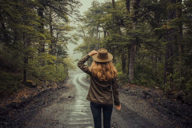 Rear view of woman standing on road in forest
