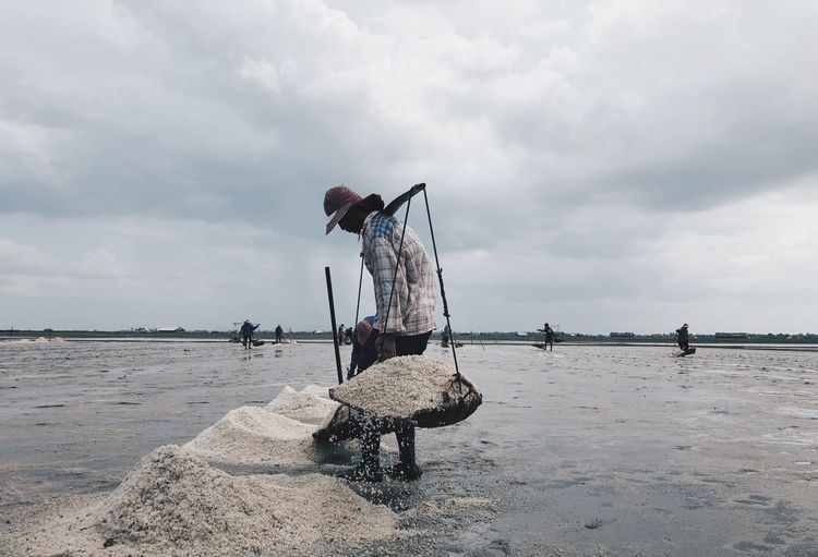 Side view of man carrying salt in baskets on shore against cloudy sky