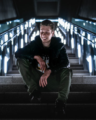 Low angle view of smiling young man sitting on illuminated steps