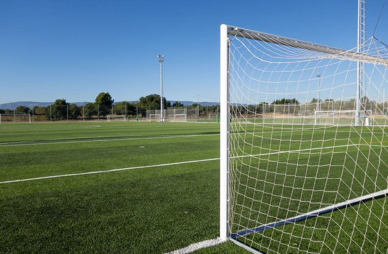 Football field with green grass Sport Grass Soccer Team Sport Sky Soccer Field Plant Nature Playing Field Field Land No People Football Sports Equipment Net - Sports Equipment Green Color Soccer Goal Day Goal Post Outdoors
