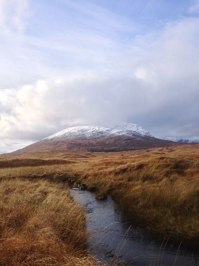 View of a small river or creek streaming through the brown grass plain with the snow-capped mountains in the background; Glencoe, Scotland, UK Creek River Remote Hiking Brown Grass Europe United Kingdom Scottish Highlands Scotland Glencoe Adventure Panorama Sky Cloud - Sky Land Beauty In Nature Nature Landscape Water Scenics - Nature Tranquility Environment Tranquil Scene Mountain No People Non-urban Scene Outdoors Snow Snowcapped Mountain My Best Photo 17.62°