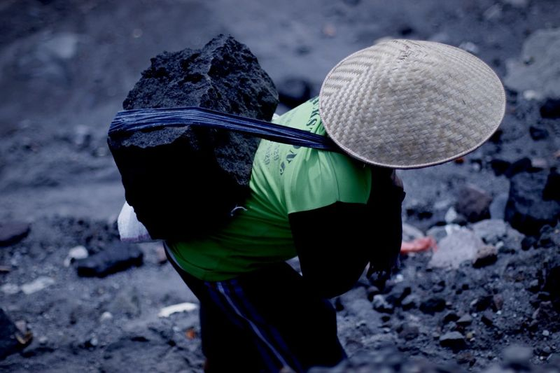 High angle view of person carrying coal on his back