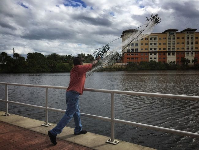 Casting for mullet Crane Creek Melbourne Florida One Man Only Casting Cast Net Casting A Net Railing Real People Riverscape Built Structure Building Exterior One Person