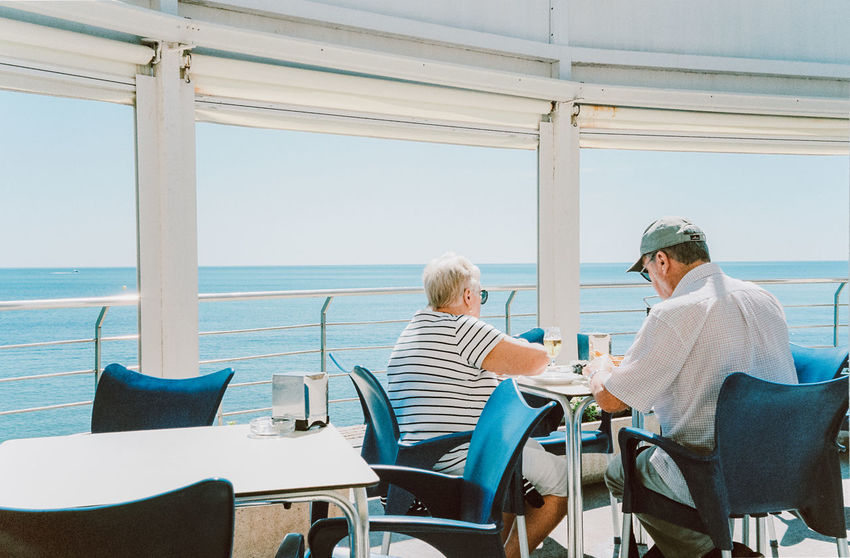 Adult Casual Clothing Chair Couple - Relationship Horizon Over Water Leisure Activity Men Outdoors Real People Rear View Sea Seat Senior Adult Senior Men Senior Women Sitting Sky Togetherness Two People Water Women