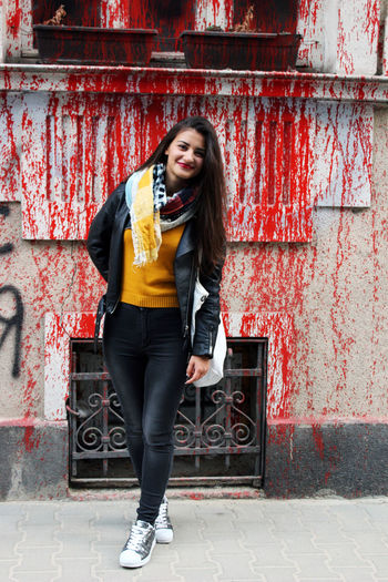 Full length portrait of young woman standing against splattered wall