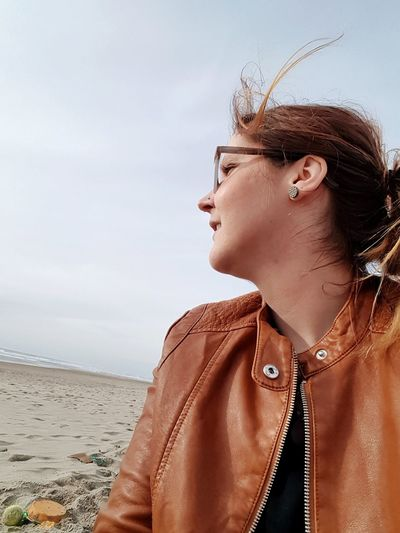 Smiling Woman Looking Away While Sitting At Beach Against Sky