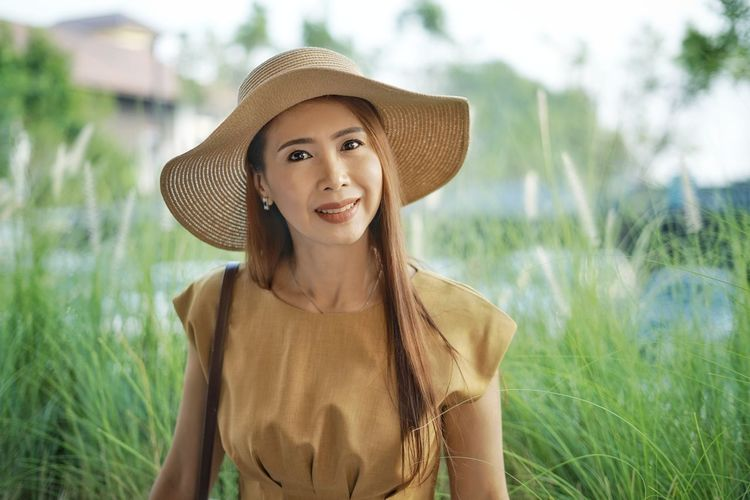 Portrait of smiling young woman wearing hat on field
