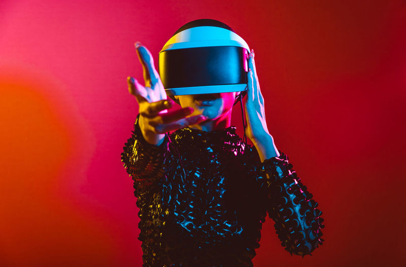 Young woman with shaved head wearing virtual reality glasses against pink background