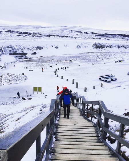 Rear view of people on snow covered landscape against sky