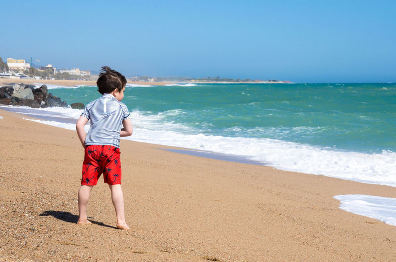 A boy plays near the sea on the beach at Santa Susanna in Spain. Happiness Happy Holiday Young Beach Beauty In Nature Boy Child Childhood Horizon Land Leisure Activity Motion One Person Outdoors Real People Rear View Sand Santa Susanna Sea Shorts Sky Vacation Water Wave