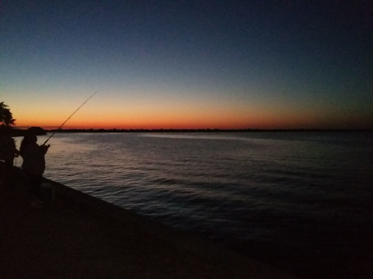 fishing, sea, fishing pole, fishing rod, water, tranquil scene, horizon over water, nature, sunset, real people, one person, tranquility, scenics, standing, weekend activities, idyllic, silhouette, beauty in nature, clear sky, leisure activity, outdoors, fishing tackle, men, sky, full length, day, people