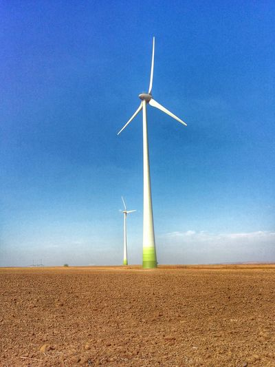 Low angle view of windmill on field against clear blue sky