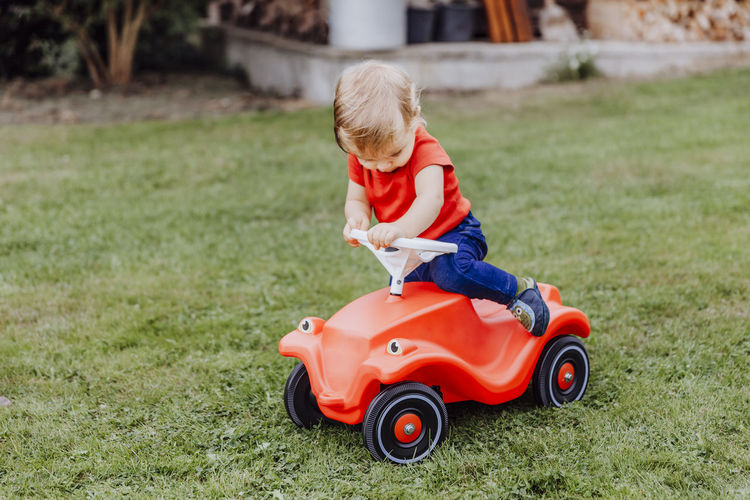 Baby girl sitting on red toy car in lawn