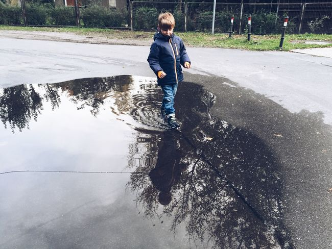 Boy walking through huge puddle of rain water Autumn Boy Child Childhood Crossing Fall Fun Hugging A Tree Obstacle Passing Puddle Rain Rainbow Reflection Sky Street Water