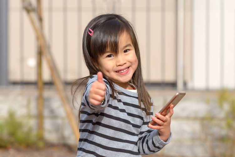 Portrait of a smiling girl holding smart phone