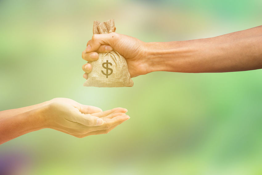 Man hand holding money bag and giving money to another person on blurred green nature background. Money concept. Conceptual paying for exchanges Receive Body Part Buying Concept Finger Giving Giving Money Hand Holding Human Body Part Human Hand Money Bag Moneybag Paying People Real People Receiving Two People Wealth