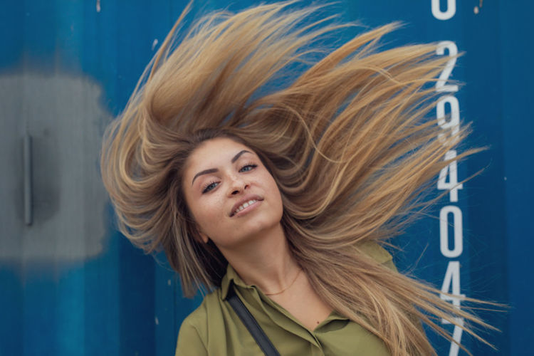 Portrait of smiling young woman tossing hair against blue metal