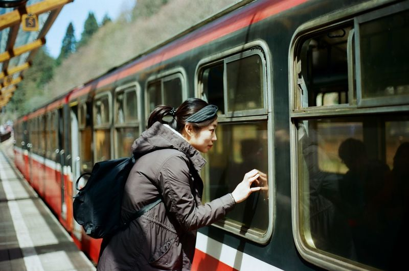 Side view of young woman looking in train window