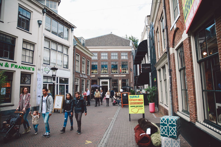 Adult Architecture Building Exterior Built Structure City City Gate City Life City Street Day Horizontal Men Outdoors People Person Retail  Road Sign Store Street Walking