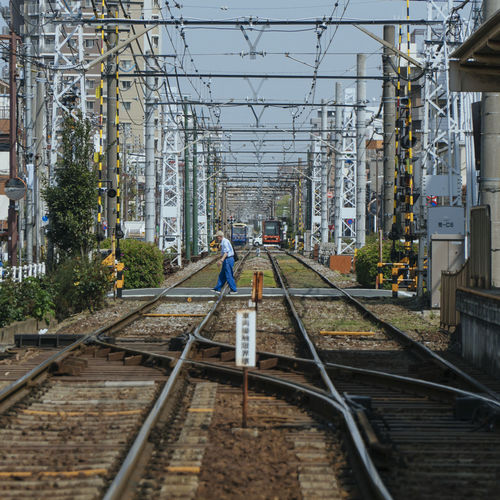 Tram in Tokyo Track Railroad Track Rail Transportation Architecture Built Structure Building Exterior Transportation Day Connection Real People The Way Forward Nature Full Length Direction Mode Of Transportation One Person Technology Cable Electricity  Men Outdoors Power Supply
