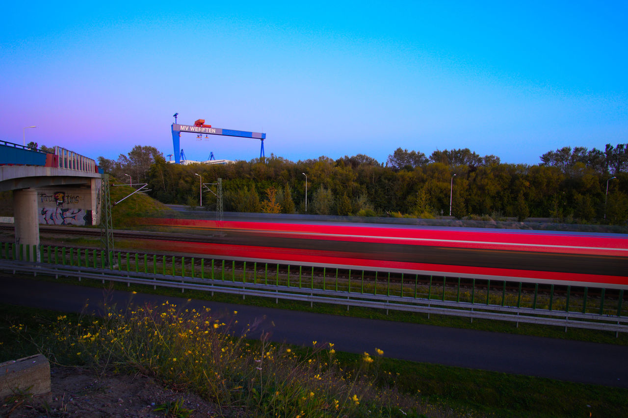 RED LIGHT TRAILS ON ROAD AGAINST BLUE SKY
