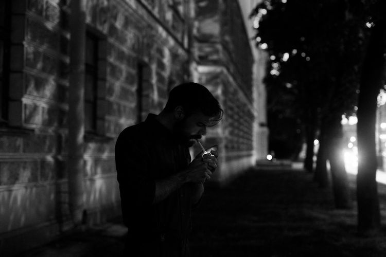Man Smoking Cigarette While Standing In City