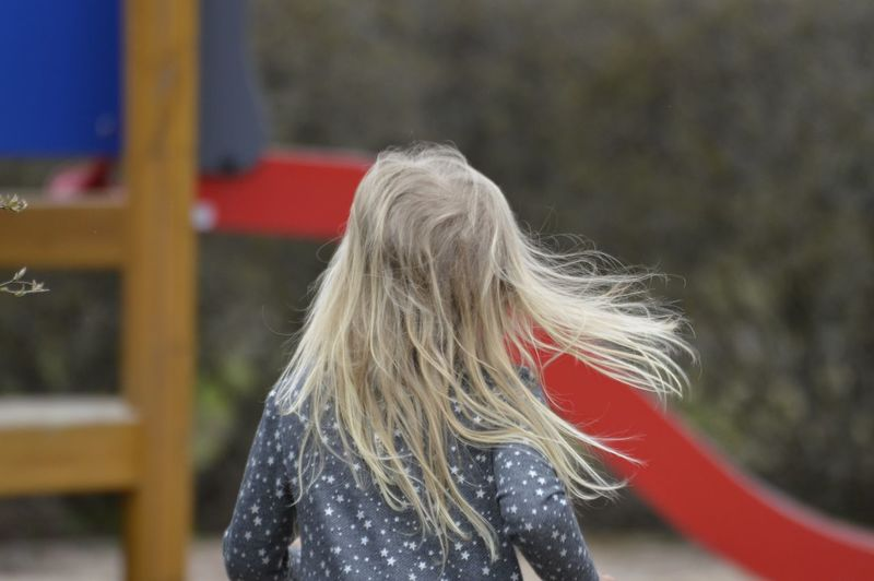 Rear view of girl with blond hair playing in playground