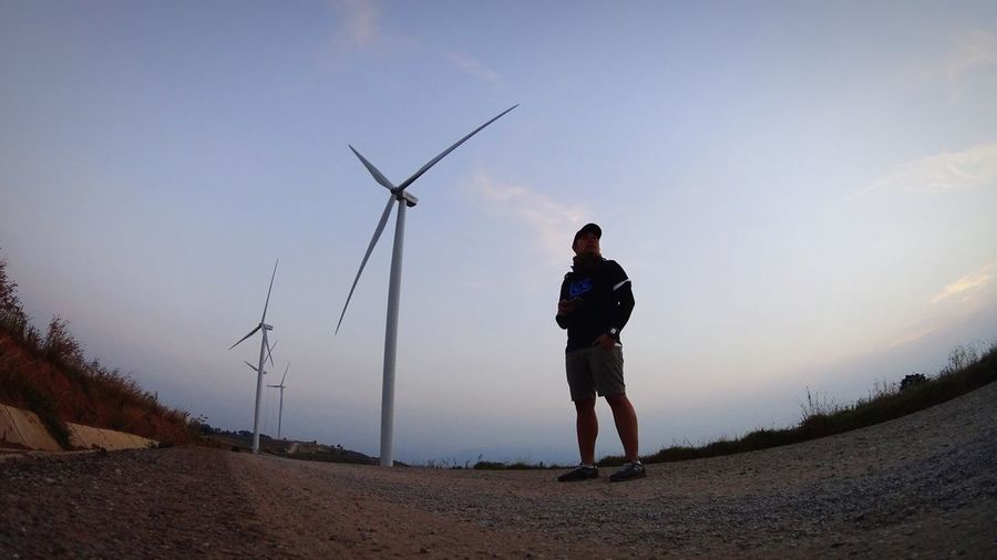 Wind Power Wind Turbine Alternative Energy Environmental Conservation Fuel And Power Generation Renewable Energy Windmill Real People Technology One Person Full Length Industrial Windmill Field Casual Clothing Lifestyles Nature Standing Low Angle View Outdoors Day Thailand Early Morning The Secret Spaces