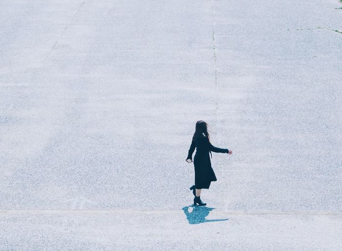 Full length side view of woman walking on road in city