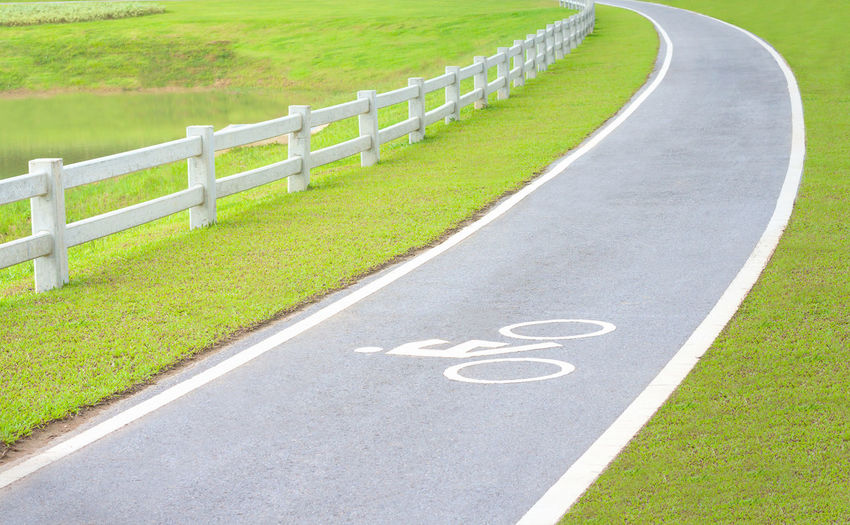bicycle lane in the park Bicycle Curve Day Empty Road Grass Green Color Lane Outdoors Road The Way Forward