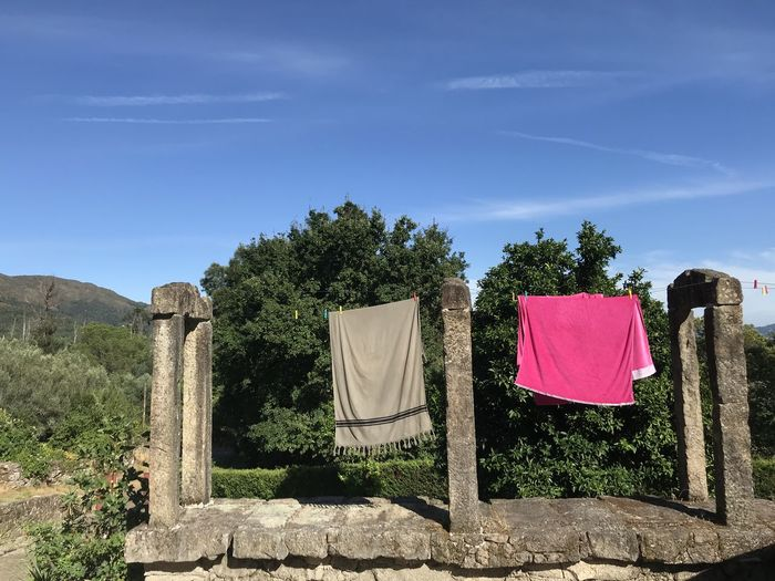 Clothes drying on field against sky